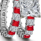An audacious De Beers ring has a princess center stone on a wide baguette-cut diamond band.