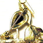 A GOLD FIFTEENTH CENTURY BROOCH IN FORM OF PELICAN STANDING ON A SCROLL RUBY DIAMOND EMERALD SAPPHIRE GARNET AMETHYST