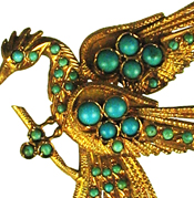 22kt Gold brooch of a bird with outstreched wings and small round turquoise beads. Pin closure, wearing