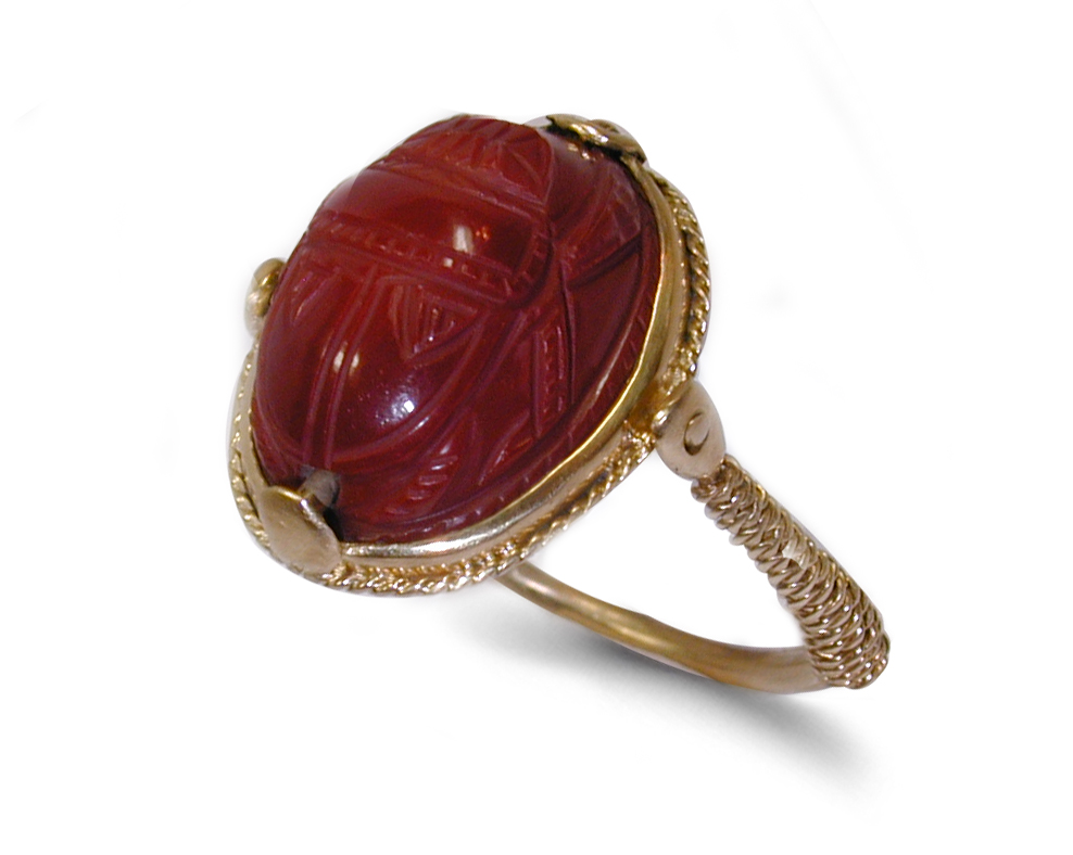 ancient gold finger scarab ring with a red cornelian scarab and scarab held in position on its gold mount by twisted gold wires which are wound round the shank